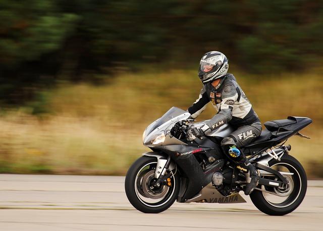 Muž v motorkárskej kombinéze s integrálnou prilbou ide na motorke.jpg