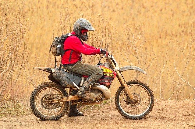 Muž na motorke v prírode celý špinavý od blata.jpg