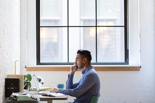 Muž sedí pod veľkým oknom, pozerá do počítača a premýšľa.jpg