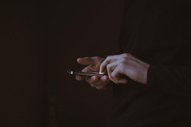 Muž v čiernom oblečení pracuje s mobilným telefónom